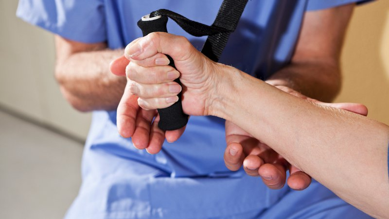 A hand therapist helps a patient.