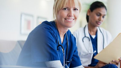 A nurse and physician review a patient file.