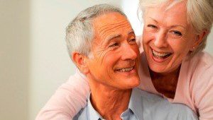 An older couple is laughing together.