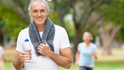 An older man is exercising in the park.