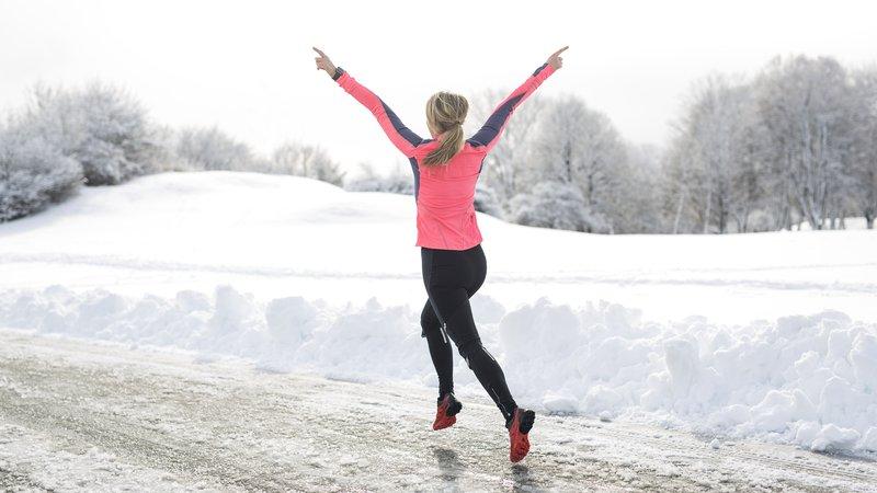 A woman runs in the snow.