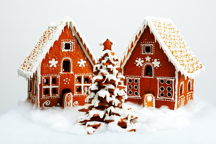 Two gingerbread houses are pictured with a tree in the middle.