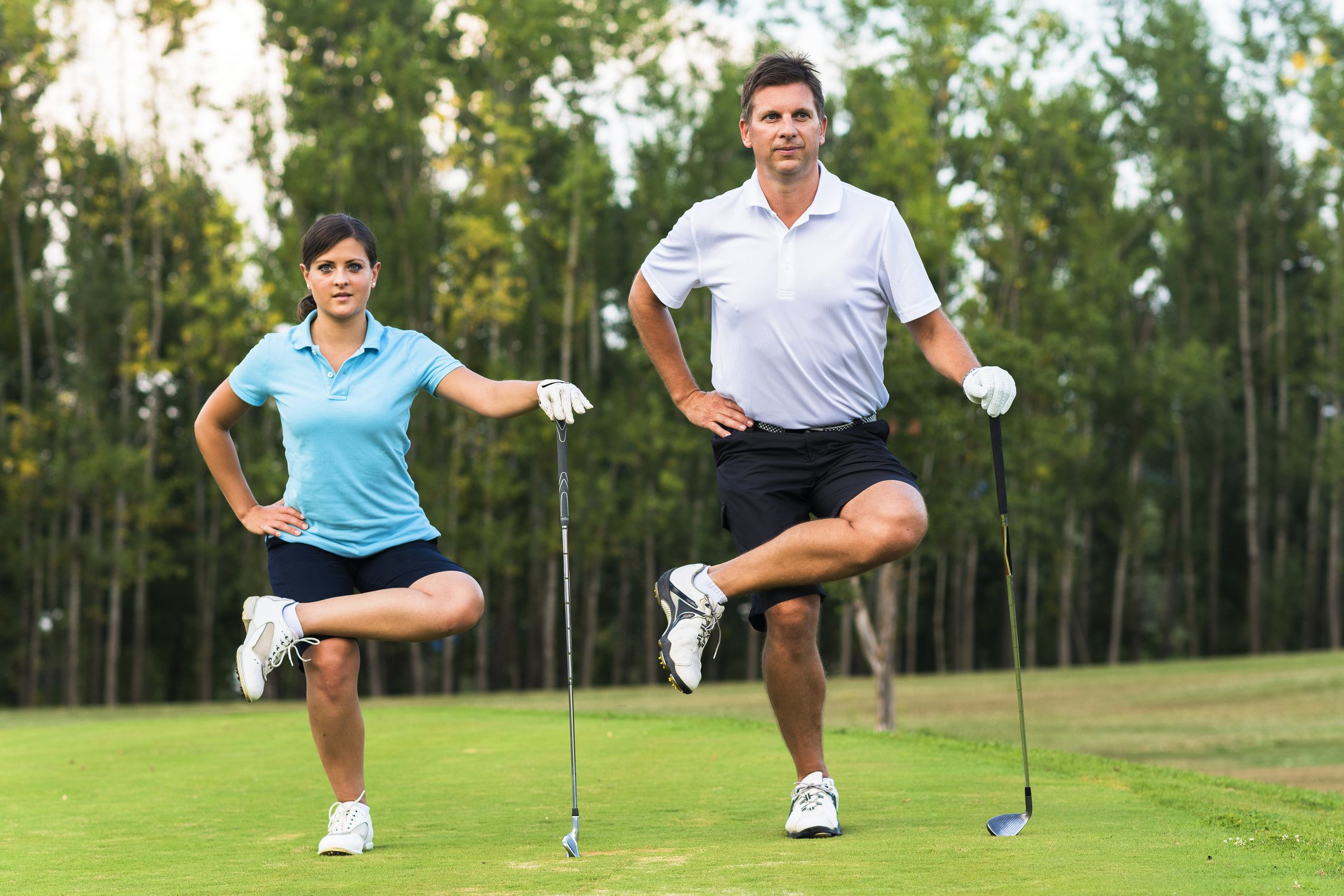 Two golfers are taking tree pose in CoxHealth's yoga for golfers class.