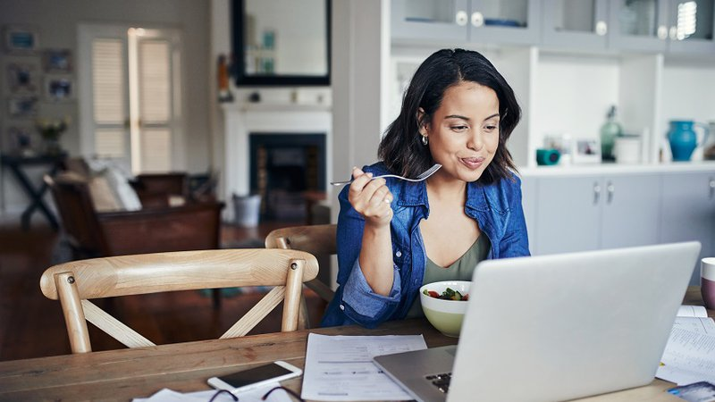 A woman eats a healthy meal while searching for health information.Classes and