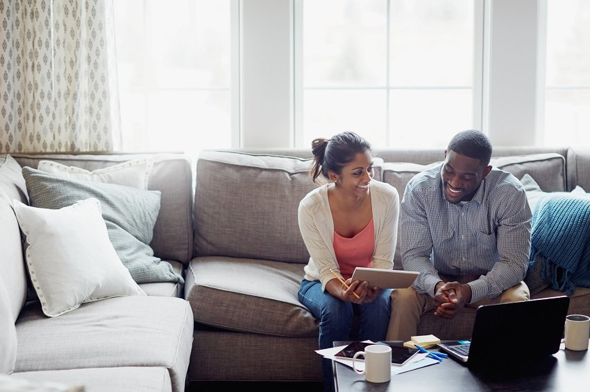 A couple looks at a computer screen.