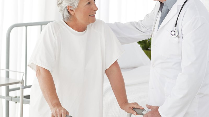 A physician helps an older patient with a walker.
