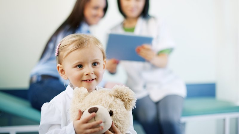 A pediatric therapy patient cuddles a teddy bear.