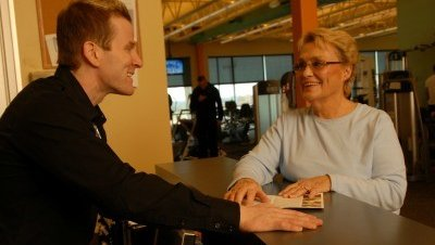 A Cox Fitness Center Branson employee discuss rates and membership guidelines with a potential member.