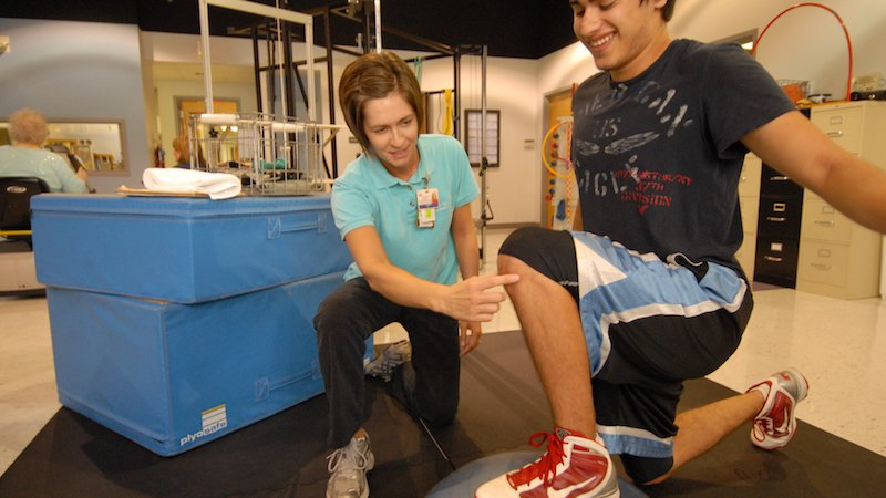 A therapist helps a patient during physical therapy.