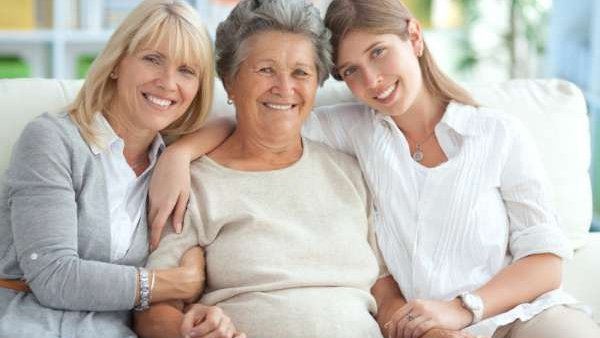 A smiling woman sits with her grown daughter and teenage granddaughter.