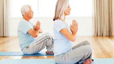 An older couple practices yoga.