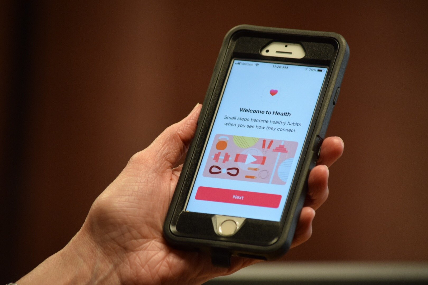 An individual holds an iPhone and prepares to use the Apple Health app.
