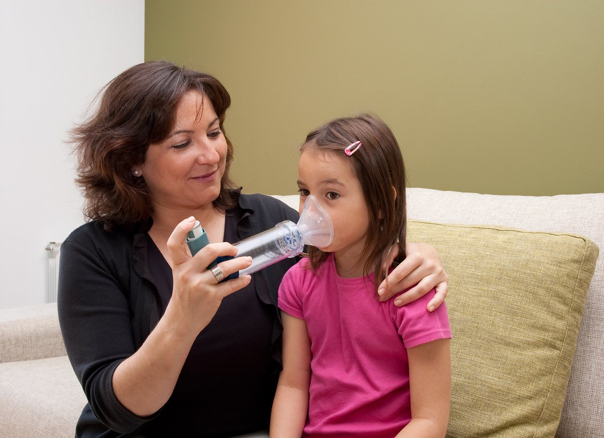 A young girl uses an inhaler.