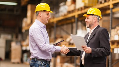 Wearing hard hats, a CoxHealth Network representative and his client meet in the client's warehouse.