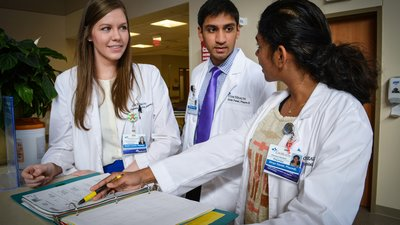 A group of CoxHealth pharmacy interns are studying patient information.