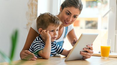 A mom and her son learn more about CoxHealth virtual visits on their computer.