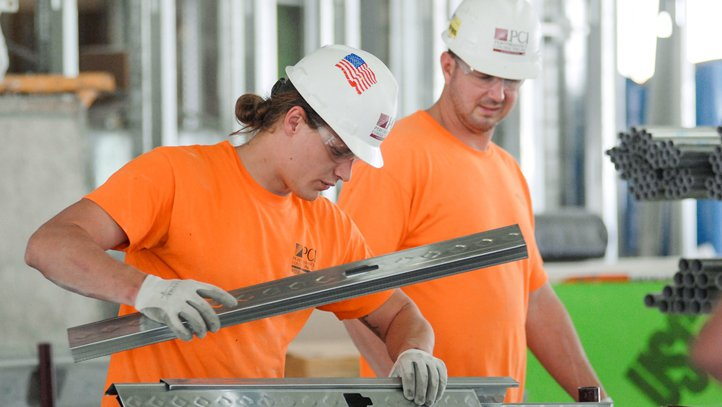 Construction workers on the job, wearing orange shirts and white hard hats.