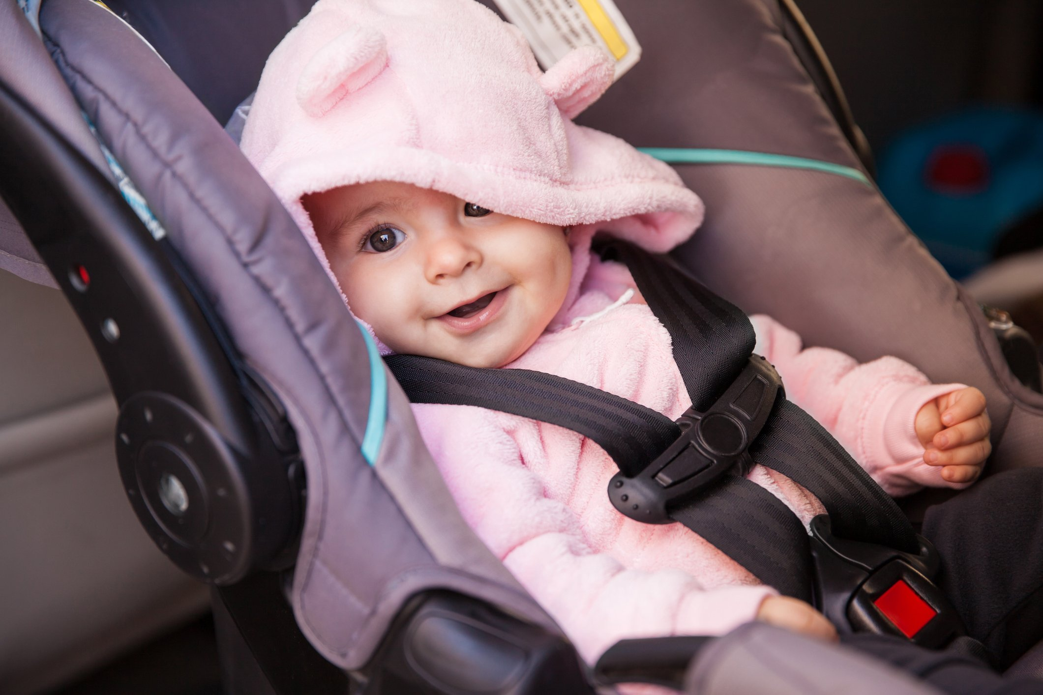 An infant is safely buckled into her car seat.