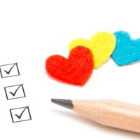 A checklist with felt hearts represents a heart screening.