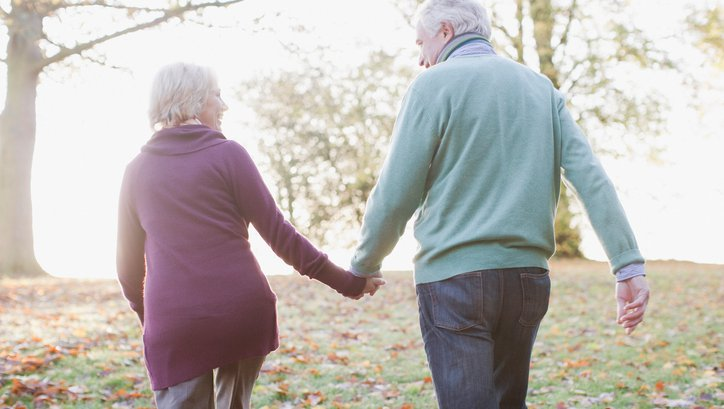 An older couple holds hands while walking through the woods.