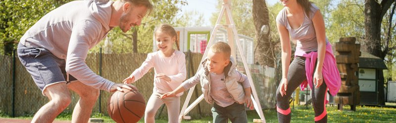 A healthy young family plays basketball outdoors.