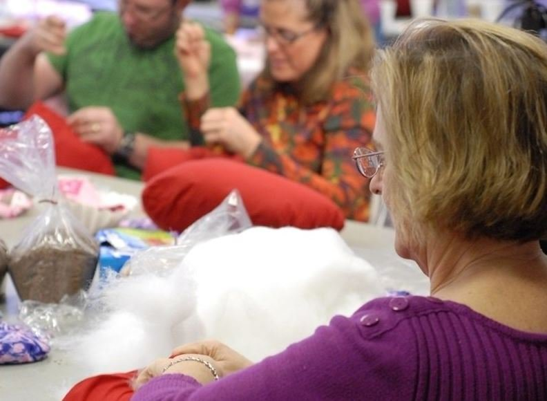Volunteers sew pillows at a sewing day.