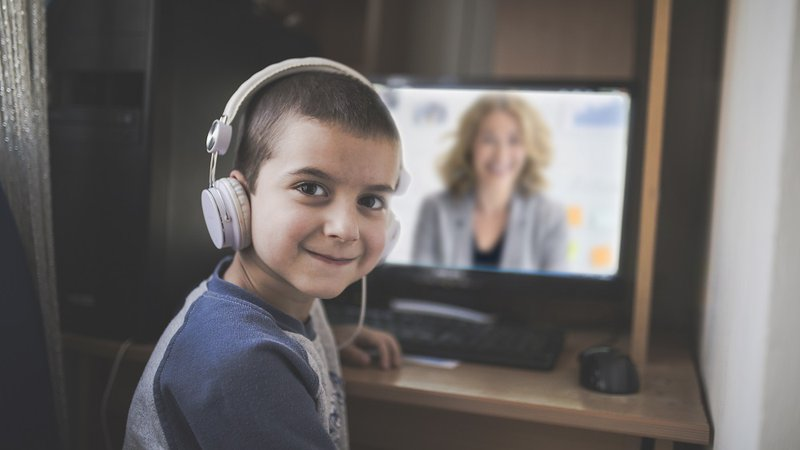 A boy uses a school computer for an online speech therapy session.