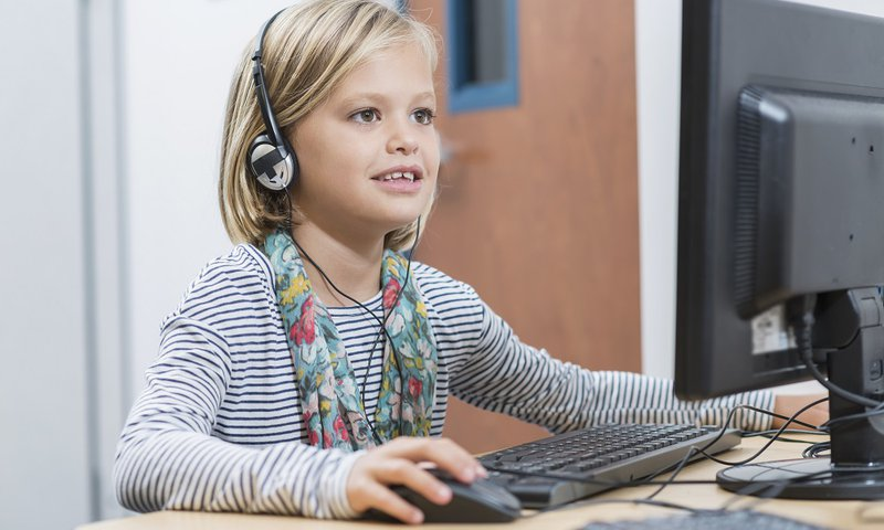 A young girl sits at a computer, wearing headphones while using CoxHealth Therapy speech therapy online.
