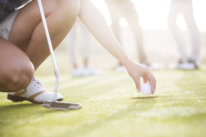 A golfer tees up.
