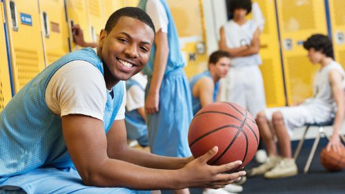 A young many holds a basketball while he sits in a locker room.